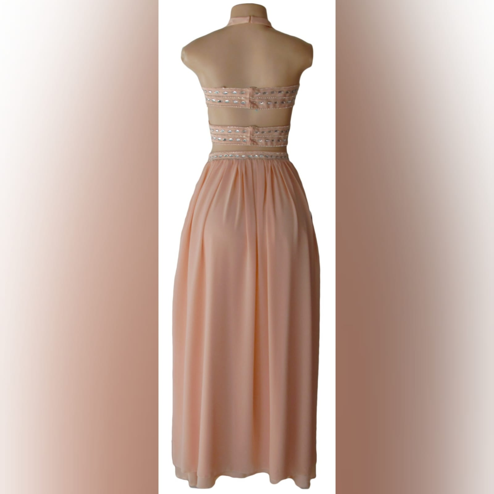 Pink nude 2 piece prom dress 3 pink nude 2 piece prom dress with crop top open on the sides, halter neck creating a v neckline with a naked back detailed with straps. Top detailed with patterned silver beading. Flowy long skirt with a slit and waistband detailed with silver beads.