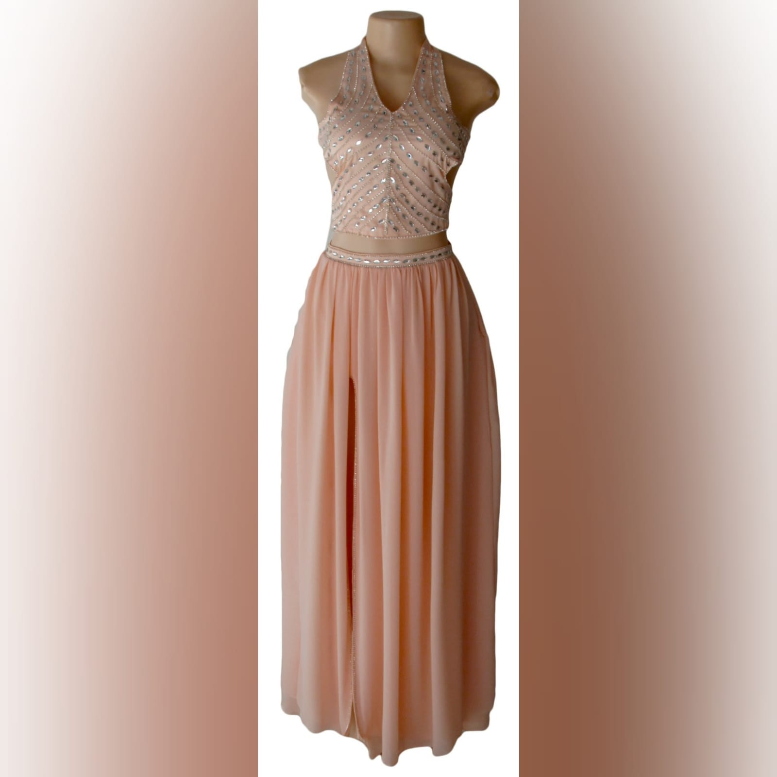 Pink nude 2 piece prom dress 6 pink nude 2 piece prom dress with crop top open on the sides, halter neck creating a v neckline with a naked back detailed with straps. Top detailed with patterned silver beading. Flowy long skirt with a slit and waistband detailed with silver beads.