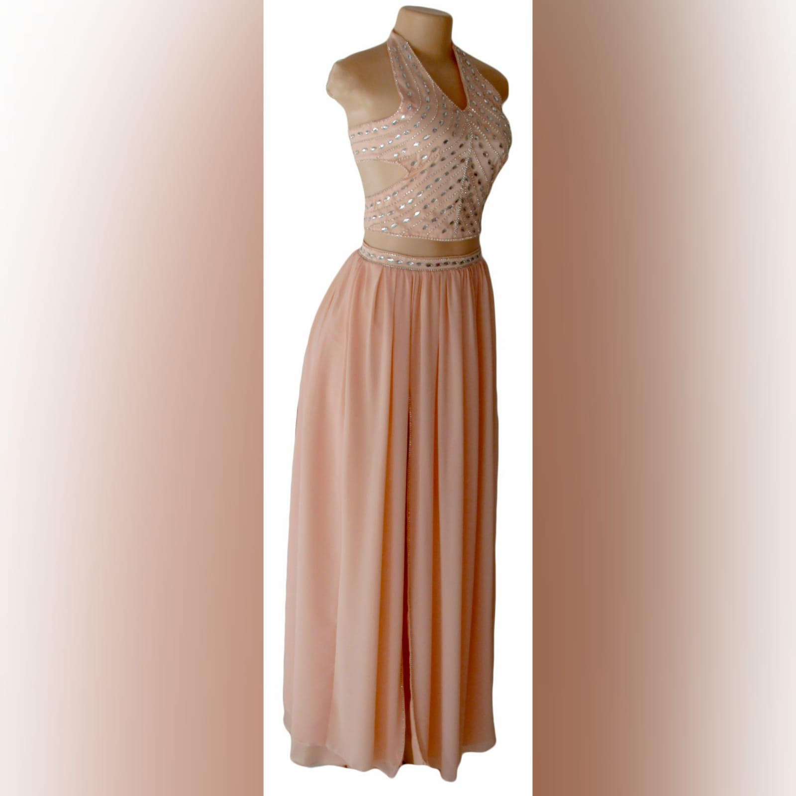 Pink nude 2 piece prom dress 7 pink nude 2 piece prom dress with crop top open on the sides, halter neck creating a v neckline with a naked back detailed with straps. Top detailed with patterned silver beading. Flowy long skirt with a slit and waistband detailed with silver beads.