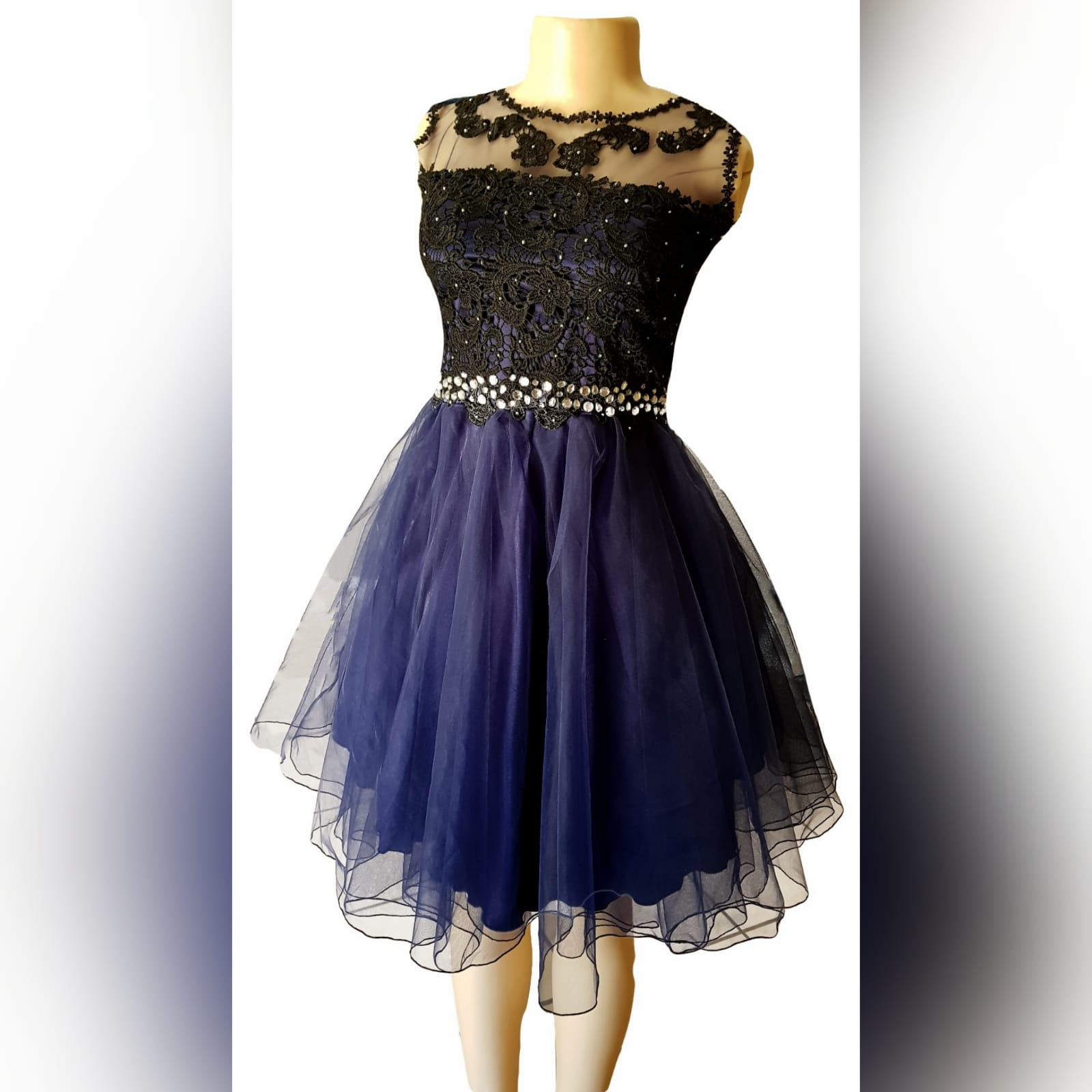 Navy blue short evening dress 2 this adorable navy blue short evening dress was created for a debutante's ball. With an illusion neckline detailed with lace to add sophistication to the design, scattered silver beads on the lace. A silver beaded belt effect to enhance the waistline, with a cute knee-length tulle skirt