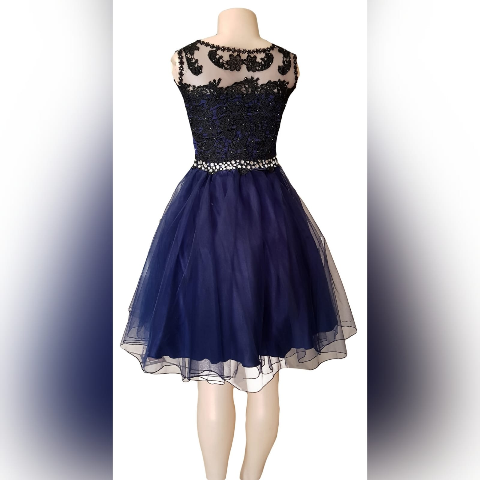 Navy blue short evening dress 4 this adorable navy blue short evening dress was created for a debutante's ball. With an illusion neckline detailed with lace to add sophistication to the design, scattered silver beads on the lace. A silver beaded belt effect to enhance the waistline, with a cute knee-length tulle skirt