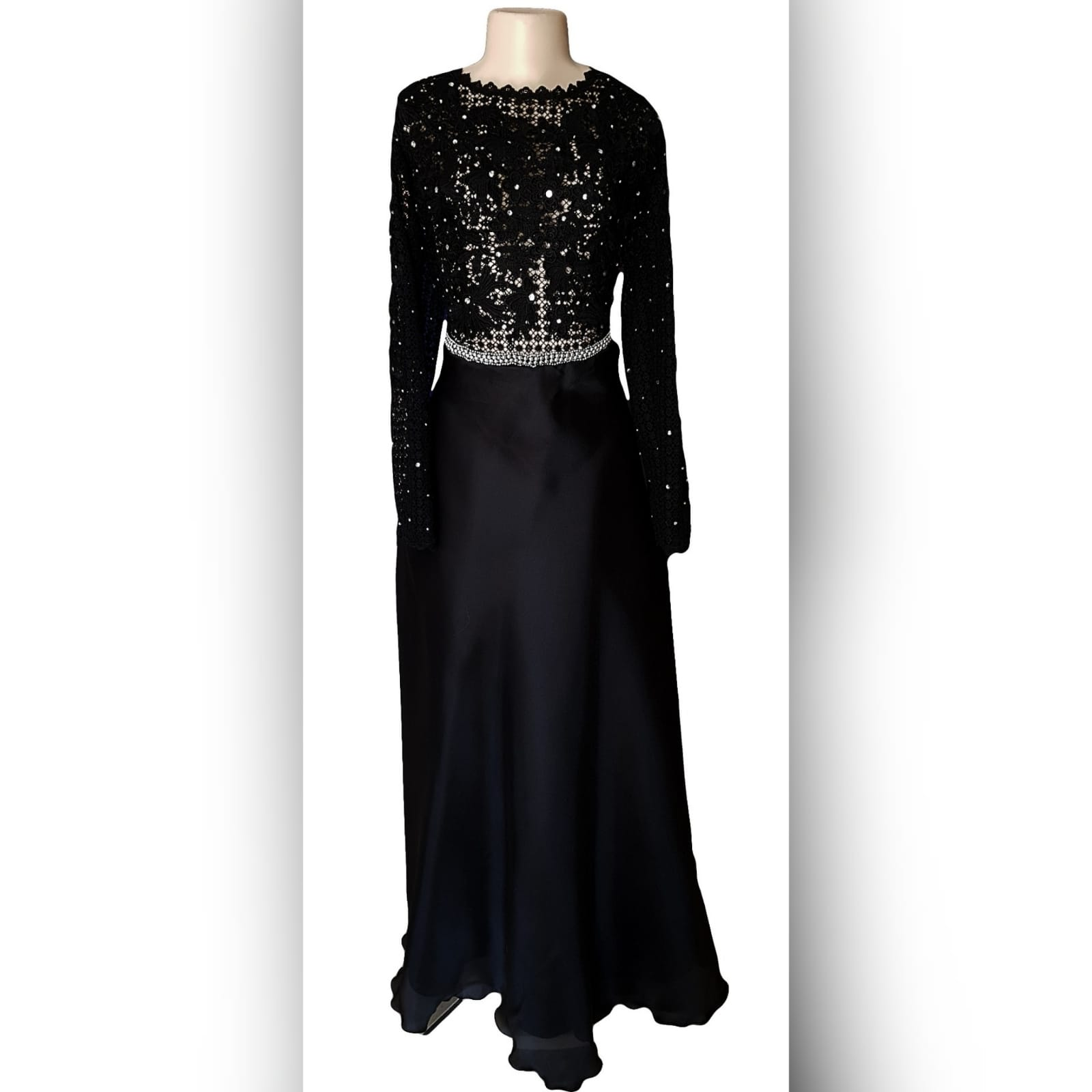 Black prom dress with a lace bodice 8 an elegant design created for a prom night. Black prom dress with a lace bodice with a slight sheer look detailed with silver beads and waist belt. Round neckline and long sleeves bottom flowy in a bridal organza