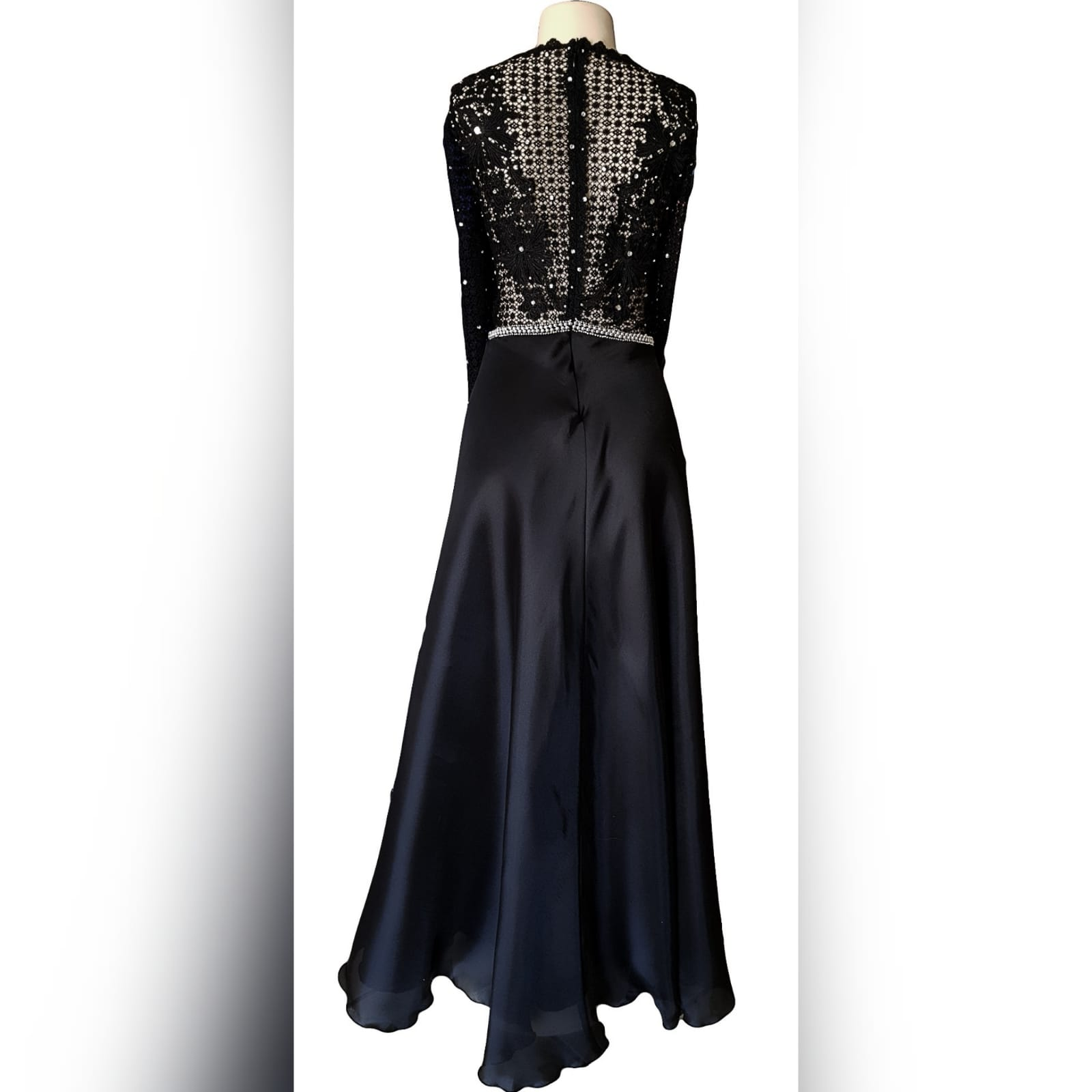 Black prom dress with a lace bodice 9 an elegant design created for a prom night. Black prom dress with a lace bodice with a slight sheer look detailed with silver beads and waist belt. Round neckline and long sleeves bottom flowy in a bridal organza